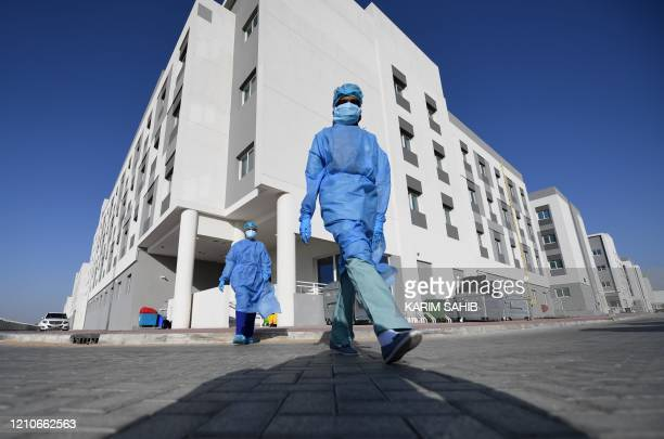 Health workers wearing protective outfits are pictured in front of a building in the Warsan neighbourhood where people infected or supected of being...