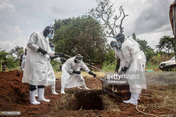 Health workers wearing protective suits as a precaution lower the body of a covid-19 victim for burial at a graveyard in Gulu, northern Uganda. The...