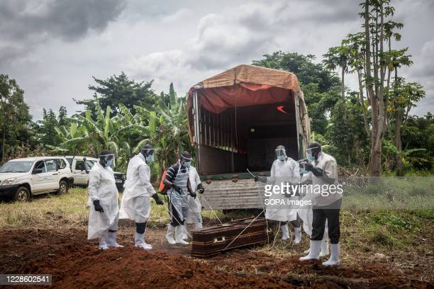 Health workers wearing protective suits as a precaution take the body of a covid-19 victim for burial at a graveyard in Gulu, northern Uganda. The...