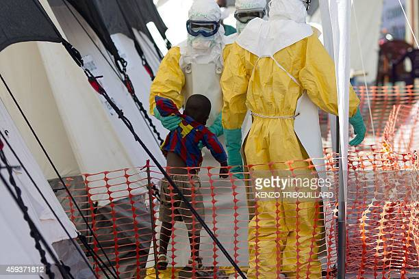 Health workers wearing protective suits assist a young patient at the Ebola treatment centre run by French Red Cross in Macenta on November 21 2014...