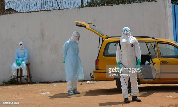 Health workers wearing protective suits await on September 23 2014 outside the Island Clinic a new Ebola treatment centre that opened in Monrovia The...