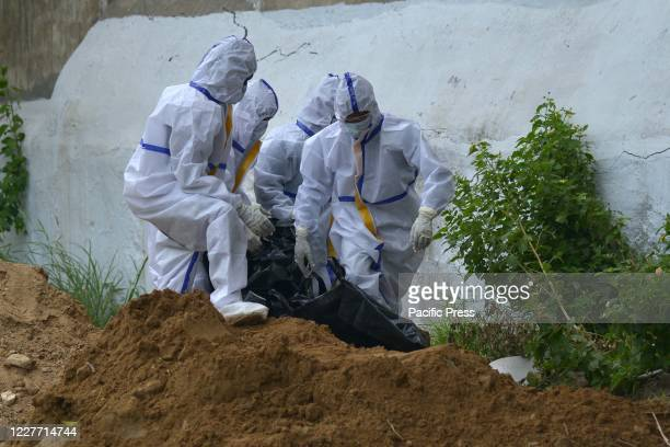 Health workers wearing protective suits buried the body of a man who died from the novel coronavirus pandemic in a christian cemetery