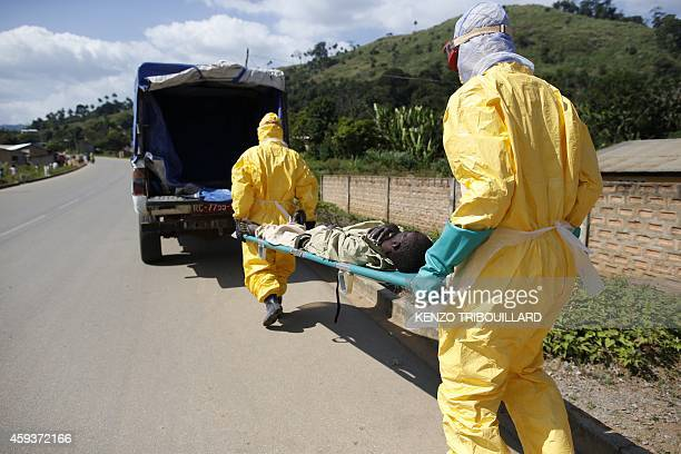 Health workers wearing protective suits carry a patient suspected of having Ebola on their way to an Ebola treatment centre run by the French Red...