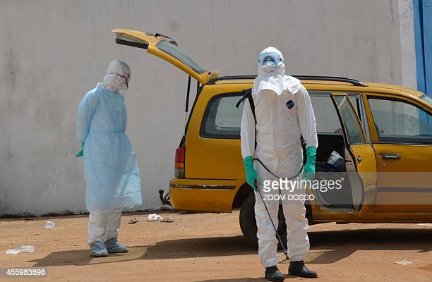 Health workers wearing protective suits disinfect a taxi on September 23 2014 outside the Island Clinic a new Ebola treatment centre that opened in...