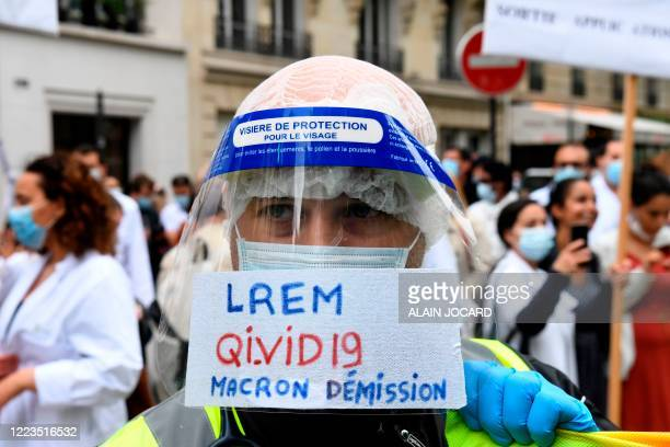 """Health workersports a face shield reading """"LREM QIVID 19 Macron resignation"""" during a demonstration, as part of a nationwide day of protests to..."""
