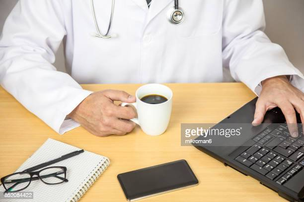 Healthcare And Medicine. Doctor taking a coffee-break and using laptop. Medical concept
