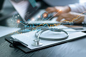 Healthcare business graph data and growth, Stethoscope with doctor's health report clipboard on table, Medical examination and doctor analyzing medical report on laptop screen.