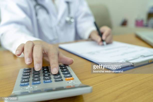healthcare costs and fees concept.hand of smart doctor used a calculator for medical costs in modern hospital. - fee stock pictures, royalty-free photos & images