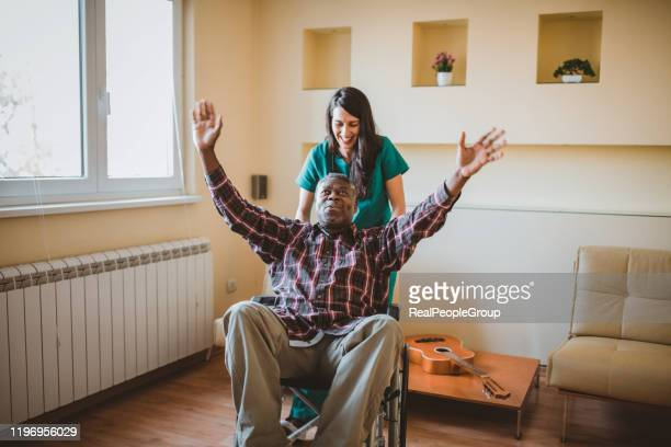 healthcare female worker is helping her disabled afro-american patient - african american man helping elderly stock pictures, royalty-free photos & images