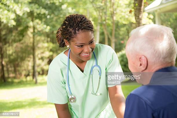 Healthcare: Kind nurse talks with senior man outside. Nursing home.