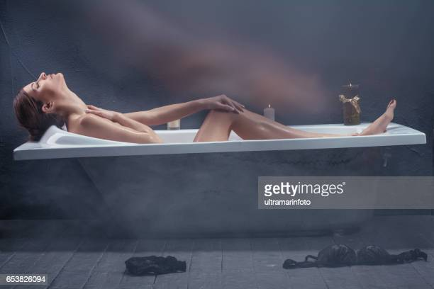 Healthcare & Medicine Beautiful woman relaxing in bathtub with lighted candles Retro old style bathroom Beauty & Wellness