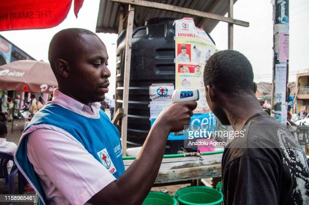 Healthcare member of UNICEF examines a man for Ebola suspicion to take precautions against the disease in Goma, Democratic Republic of the Congo on...