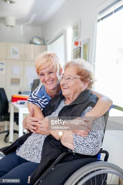 gesundheitswesen-krankenschwester umarmt senior woman in dem seniorenheim - hingabe stock-fotos und bilder