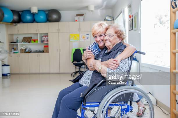 healthcare nurse embracing senior woman in the retirement home - residential care stock photos and pictures