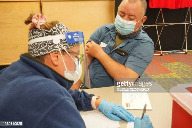 Healthcare prepares to vaccinate a man with the Covid-19 vaccine on April 30 as the Pasadena Public Library hosts a mobile vaccine clinic set up by...