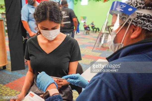Healthcare prepares to vaccinate a woman with the Covid-19 vaccine on April 30 as the Pasadena Public Library hosts a mobile vaccine clinic set up by...
