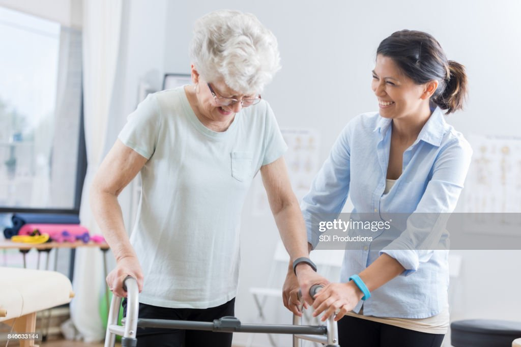 Healthcare professional helps senior woman walk with a walker : Stock Photo