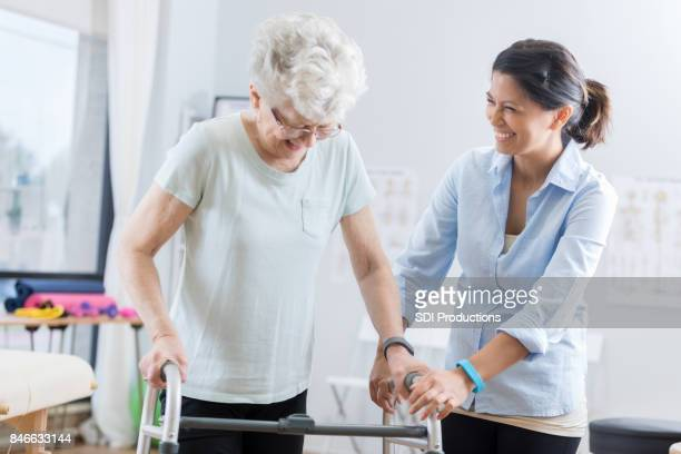 healthcare professional helps senior woman walk with a walker - bounce back stock photos and pictures