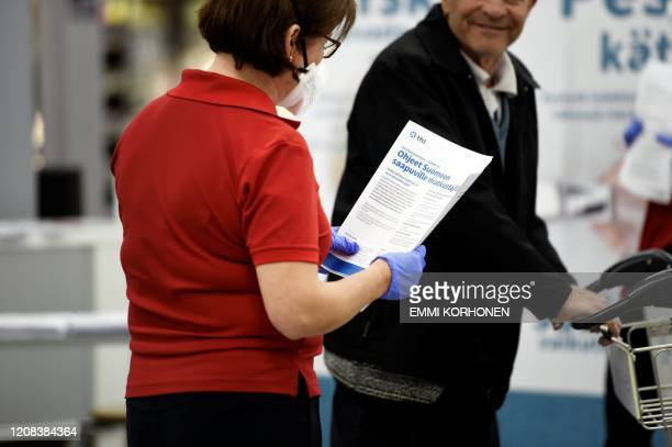 A healthcare professional in protective gear greets an incoming tourist at the Helsinki Airport in Vantaa Finland on March 27 2020 A large number of...