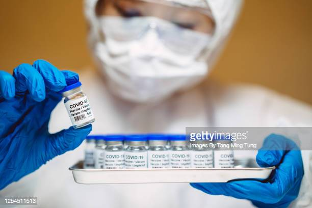 healthcare professional in protective gloves & workwear holding & organising a tray of covid-19 vaccine vials - china coronavirus stock pictures, royalty-free photos & images
