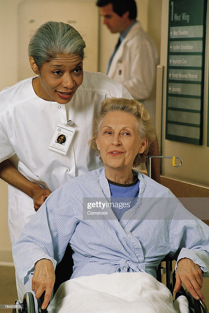 Healthcare professional pushing patient in wheelchair : Stockfoto