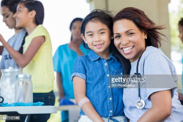 healthcare professional volunteering during health fair - film and television screening stock pictures, royalty-free photos & images
