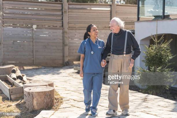 Healthcare professional walks outdoors with elderly man on nursing home campus.