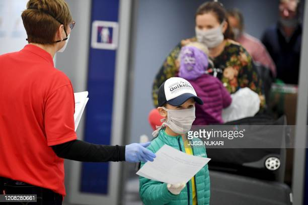 Healthcare professionals and Finnish Red Cross volunteers meet arriving tourists from the Finnair flight from Bangkok at the airport in Vantaa...