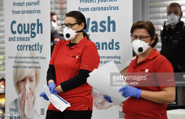Healthcare professionals and Finnish Red Cross volunteers wearing face masks wait to greet arriving passengers at the Airport in Vantaa Finland on...