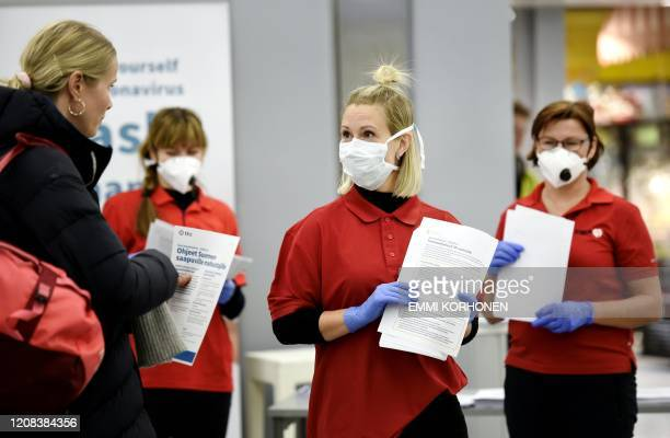 Healthcare professionals in protective gear greet incoming tourists at the Helsinki Airport in Vantaa Finland on March 27 2020 A large number of...