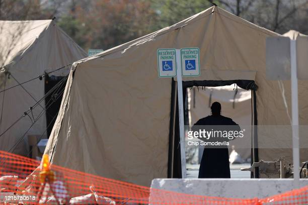 Healthcare professionals prepare to screen people for the coronavirus at a testing site erected by the Maryland National Guard in a parking lot at...