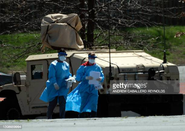 Healthcare professionals screen people at a testing site origanized by the Maryland National Guard in a parking lot at FedEx Field on March 30, 2020...