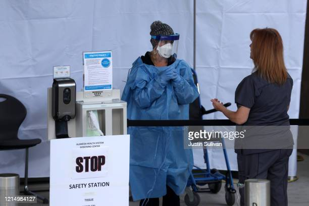 Healthcare professionals screen people entering the emergency room at Highland Hospital on March 26, 2020 in Oakland, California. Dozens of health...