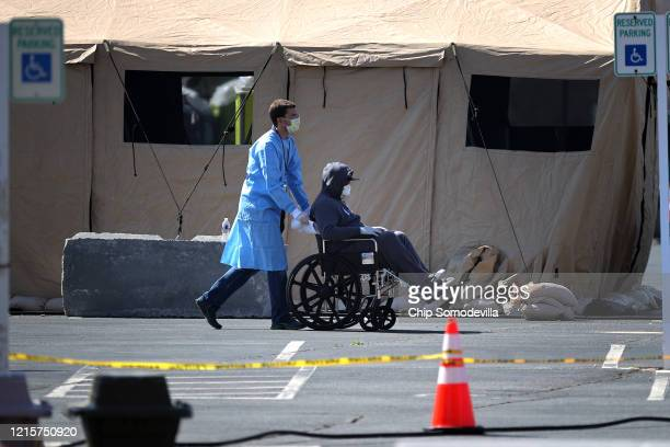 Healthcare professionals screen people for the coronavirus at a testing site organized by the Maryland National Guard in a parking lot at FedEx Field...
