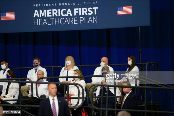 Healthcare professionals sit on stage and watch as US President Donald Trump delivers remarks on his healthcare policies on September 24 2020 in...