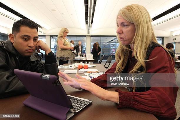 Healthcare reform specialist Naama Pozniak helps Edgar Loya compare plans at the free Affordable Care Act Enrollment Fair at Pasadena City College on...