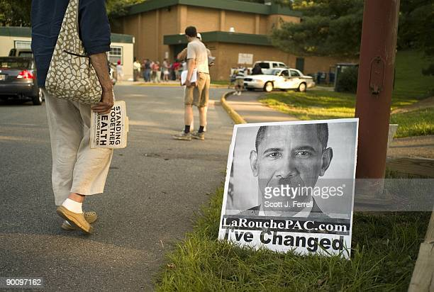 A healthcare reform supporter walks by a sign belonging to Lyndon LaRouche suppoerts outside a town hall meeting in Germantown Md hosted by Rep Donna...