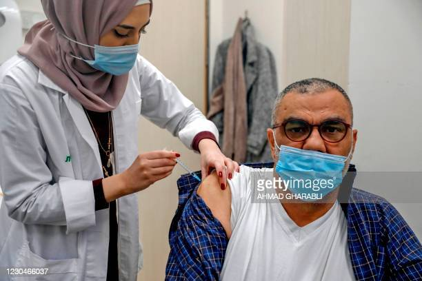 Healthcare worker administers a COVID-19 vaccine to a Palestinian man at the Clalit Health Services in the Palestinian neighbourhood of Beit Hanina,...