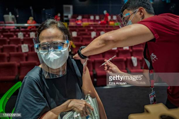 Healthcare worker administers a dose of Sinovac Biotech's CoronaVac vaccine to a woman at a mall theatre converted into a vaccination centre on June...