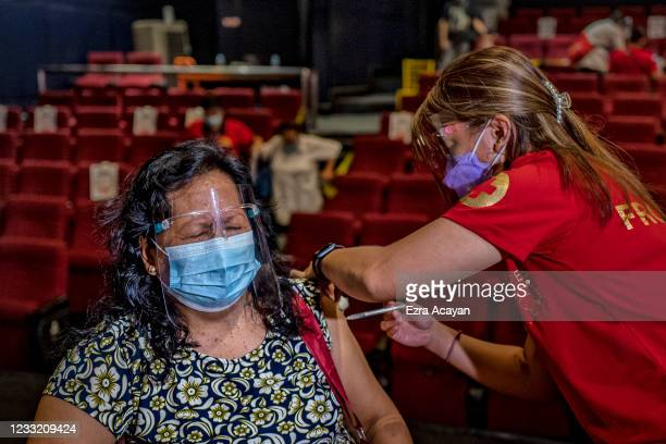 Healthcare worker administers a dose of Sinovac Biotech's CoronaVac vaccine to an elderly woman at a mall theatre converted into a vaccination centre...