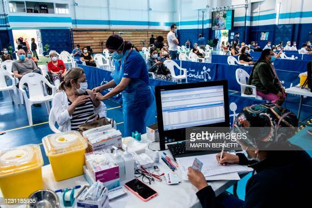 Healthcare worker administers a dose of the Chinese-made COVID-19 vaccine CoronaVac to a teacher at a vaccination centre in Santiago, on February 15...