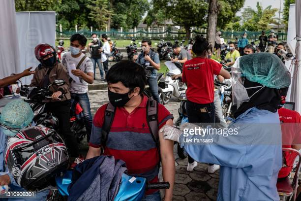 Healthcare worker administers a dose of the Sinovac Biotech Ltd. Covid-19 vaccine to a man on a motorcycle during a mass drive-thru vaccination...