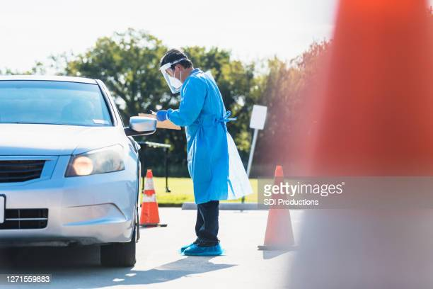 医療従事者がドライバーにコロナウイルス検査を投与 - ドライブスルー検査 ストックフォトと画像