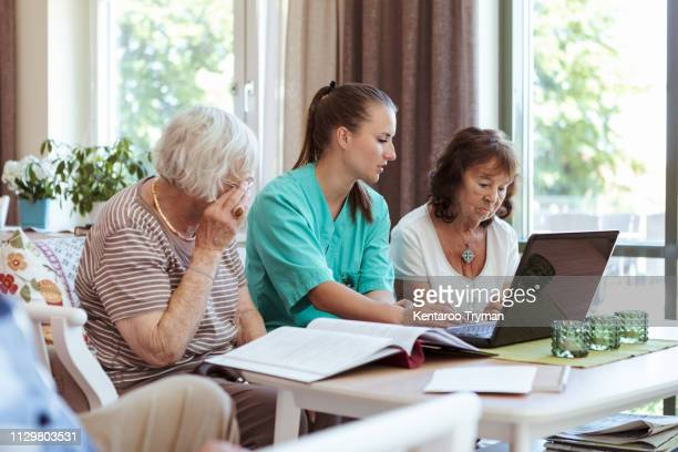 Healthcare worker and elderly women with laptop and medical reports at nursing home