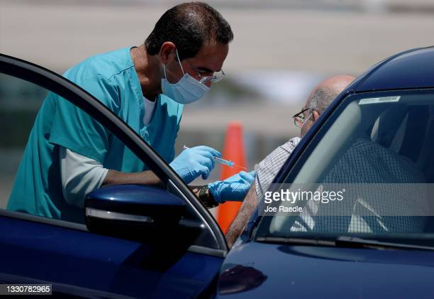Healthcare worker at a drive-thru site setup by Miami-Dade and Nomi Health in Tropical Park prepares to administer a COVID-19 vaccine on July 26,...
