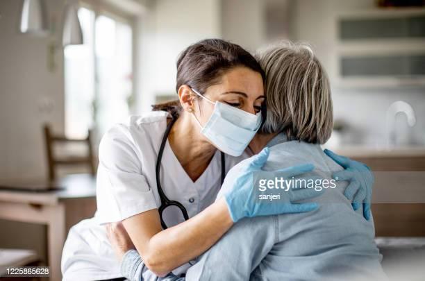 trabajador sanitario en casa - embracing fotografías e imágenes de stock