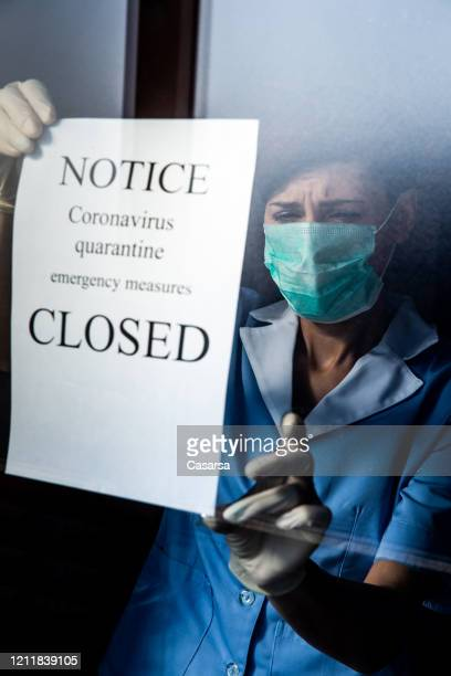 healthcare worker attaching closed sign notice for epidemic coronavirus on window - closing stock pictures, royalty-free photos & images
