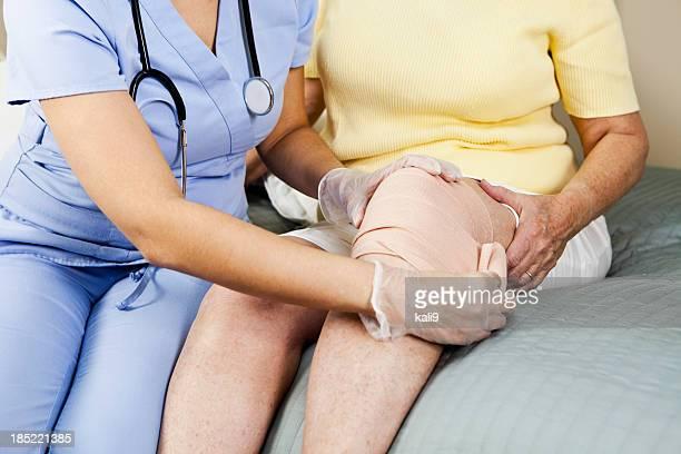 Healthcare worker bandaging patient's knee