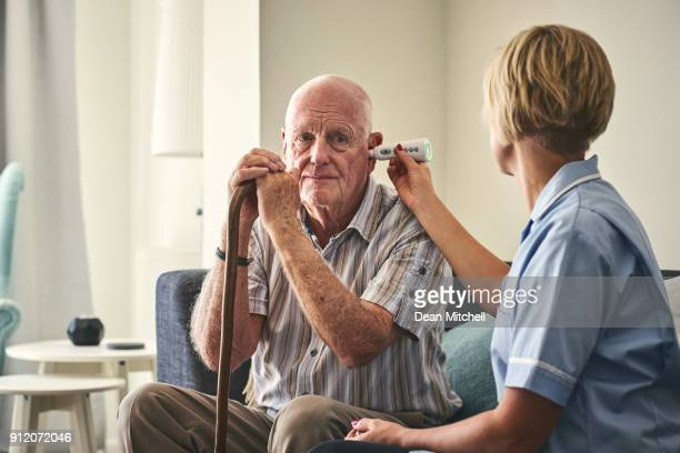 healthcare worker checking senior man's temperature - fever stock pictures, royalty-free photos & images