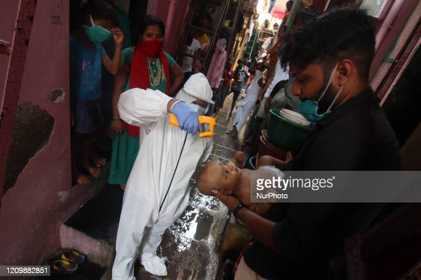 A healthcare worker checks the temperature of a baby in the Dharavi slum area of Mumbai India on April 14 2020 India continues in nationwide lockdown...